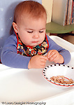 14 month old baby girl closeup sitting in high chair feeding self dry cereal (Chererios) pincer grip Caucasian vertical