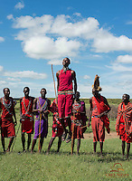 Young warriors welcome visitors to the village with a dance, Maasai village