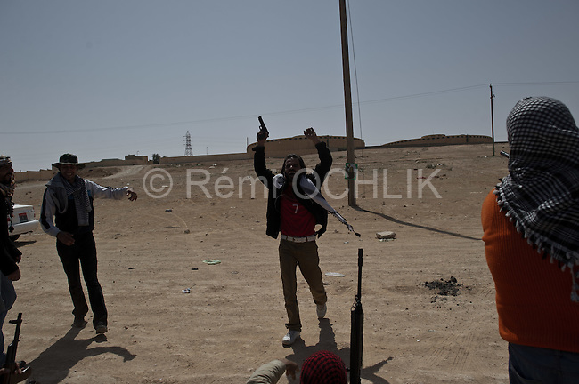 © Remi OCHLIK/IP3 - Bin Jawaad March 27, 2011 - Libyan fighters celebrate as they just took back the city of Bin Jawaad without fighting, they found the city empty from the loyalist Khadafi forces - They open fire on Khaddafi portrait with gun, AK47 or rocks