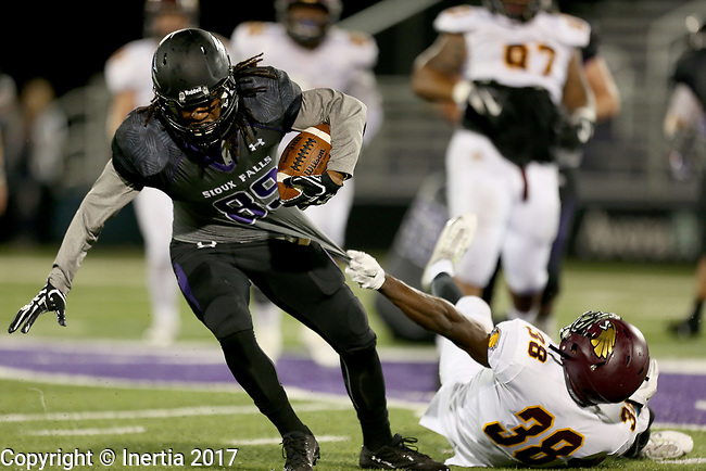 SIOUX FALLS, SD - SEPTEMBER 23: Paul Grey-Bennett #89 from the University of Sioux Falls tries to break free from Nelson Uzonwa #38 from Minnesota Crookston in the first half of their game Saturday night at Bob Young Field in Sioux Falls. (Photo by Dave Eggen/Inertia)