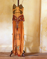 "A faded orange costume designed for the Ballet ""Thamar"" in 1912 decorated with hand-painted and appliqued gold crescent moons and an embroidered red girdle"