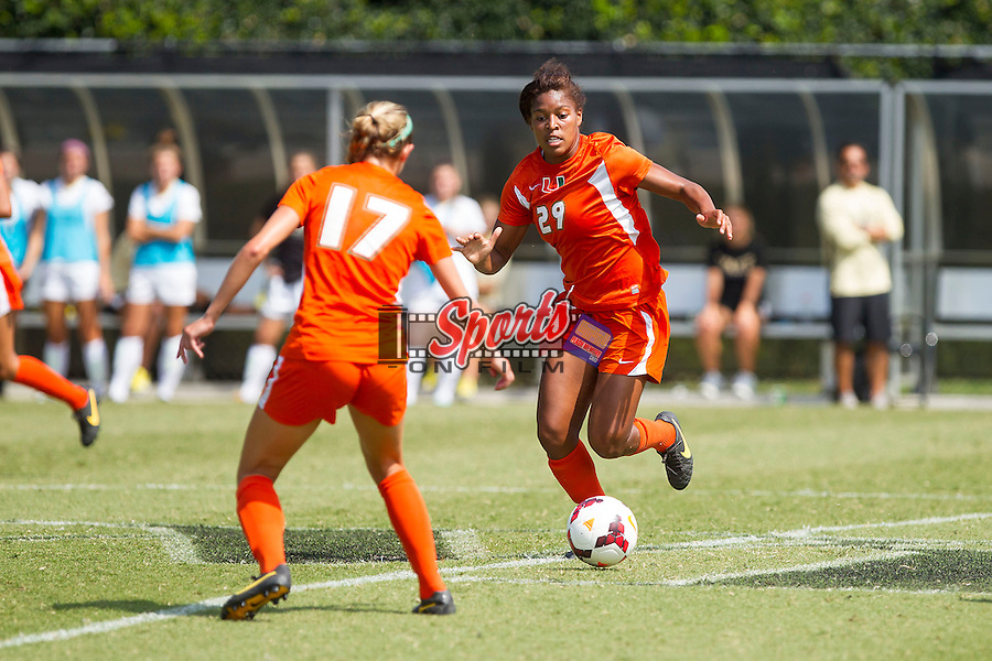 Blake Stockton (29) and Gracie Lachowecki (17) of the Miami Hurricanes chase after the ball during second half action against the Wake Forest Demon Deacons at Spry Soccer Stadium on September 15, 2013 in Winston-Salem, North Carolina.  The Deacons defeated the Hurricanes 4-0.   (Brian Westerholt/Sports On Film)