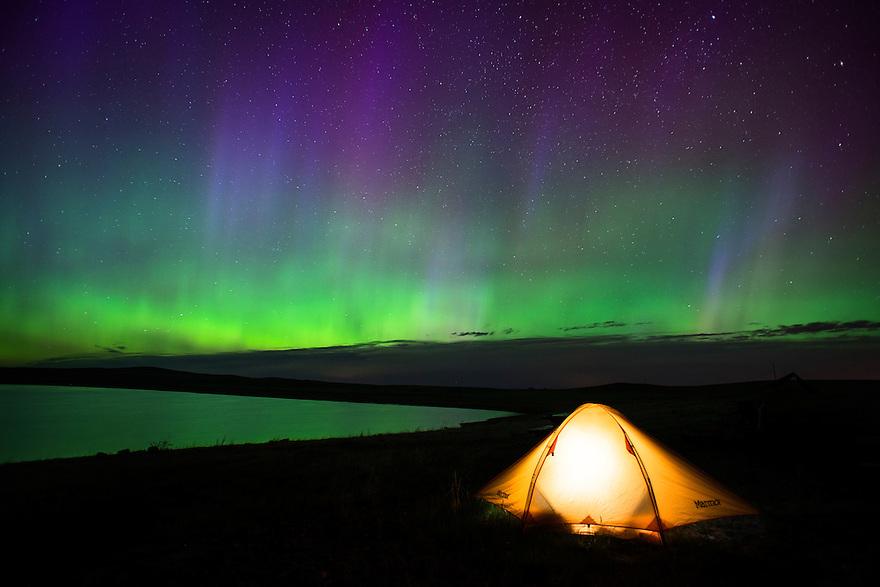 A lantern illuminates a tent beneath the aurora borealis at Bean Lake on Montana's Rocky Mountain Front Range.