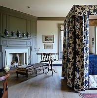 An antique wooden chaise longue is placed beside the fireplace in this panelled bedroom