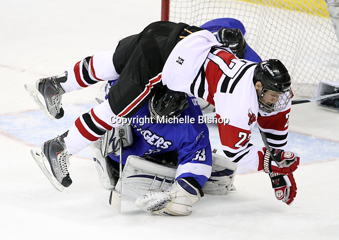 UNO's Matt Ambroz falls on top of Alabama-Huntsville goalie Clarke Saunders during the second period. Alabama-Huntsville beat UNO 2-1 in overtime Saturday night at Qwest Center Omaha. (Photo by Michelle Bishop)