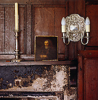A  small portrait rests on the mantelpiece in the wood-panelled living room
