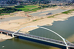 Nederland, Gelderland, Nijmegen, 26-06-2014; de nieuwe stadsbrug van Nijmegen over rivier de Waal, De Oversteek.  Links van de rivier grondwerkzaamheden voor de Dijkteruglegging Lent (Ruimte voor de Rivier).<br /> First bridge the new city bridge of Nijmegen on the river Waal, De Oversteek (The Crossing). To the left of the river groundwork for the Dike relocation of Lent (project Ruimte voor de Rivier: Room for the River).<br /> luchtfoto (toeslag op standaard tarieven);<br /> aerial photo (additional fee required);<br /> copyright foto/photo Siebe Swart.