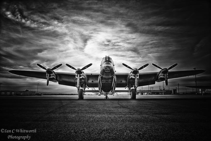 A World War II Lancaster Bomber sits on the tarmac in black and white with it's bomb bay doors open at the Canadian Warplane Heritage Museum.