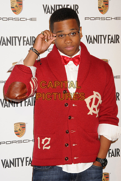 TRISTAN WILDS.Porche and Vanity Fair Celebrate the Launch of the Porche Panamera at Milk Studios, Los Angeles, California, USA..September 24th, 2009.half length cardigan knitted shawl collar hand in pocket red bow tie glasses hand leather elbow patches .CAP/ADM/BP.©Byron Purvis/AdMedia/Capital Pictures.
