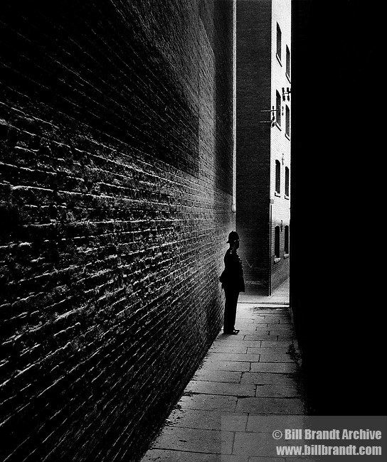 Policeman in an alley Bermondsey. Here he used the 'day for night' technique employed by cinematographers to transform images photographed in daylight into night scenes..
