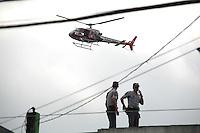 CARAPICUIBA, SP - 31.01.2012 - ASSALTO A BANCO ITAU CARAPICUIBA - Policiais procuram nos telhados por um dos assaltantes e recebem a ajuda do Aguia. Um assaltante foi morto e quatro foram presos apos tentativa de assalto em uma agencia do banco Itau, em Carapicuiba, na Grande Sao Paulo, nesta terca-feira (31), em Carapicuiba na Grande SP. Segundo a Delegacia Seccional da cidade, os criminosos entraram armados no banco, que fica na avenida Inocencio Serafico, por volta das 16h. A Polícia Militar foi acionada e a avenida bloqueada por viaturas. Houve troca de tiros. (Foto: Renato Silvestre/NewsFree)
