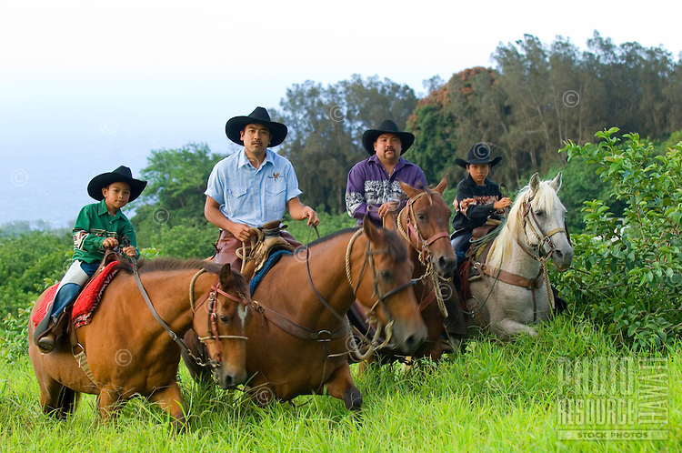 Two Hawaiian cowboys (paniolos) and their children riding on a Big Island ranch.