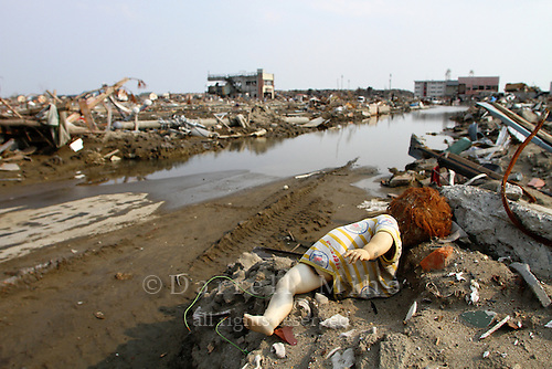 May 17, 2011; Ishinomaki, Miyagi Pref., Japan - Damage after the magnitude 9.0 Great East Japan Earthquake and Tsunami that devastated the Tohoku region of Japan on March 11, 2011...A child's doll rests on debris as the sea water begins to creep into the city of Ishinomaki. The city shifted southeast 17 feet (5.3 meters) and sank 4 feet (1.2 meters) as a result of the powerful 9.0 magnitude earthquake. Parts of the city now get flooded twice a day during high tide.