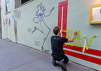 """New York, NY 18 September 2015 - French Graffiti artist L'Atlas at work on a mural. His """"abstract calligraphy"""" creats a strong contrast to the work of French graffiti artist JR and Brasilian Twins Os Gemoes whose work appears on the left."""