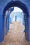 A woman in a blue gown is walking under a blue archway at the end of a stone path in a blue village in Morocco