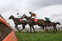 The field led by Nozic ridden by Gemma Gracey-Davison in jumping action in the Racing Plus Chase Day 230212 Handicap Chase - Horse Racing at Kempton Park Racecourse