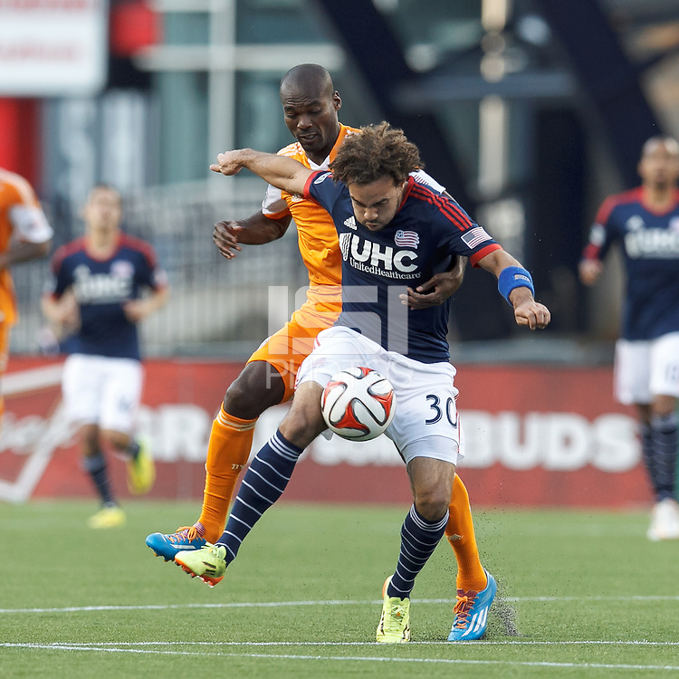 Houston Dynamo substitute forward Omar Cummings (7) fails to clear ball as New England Revolution defender Kevin Alston (30) gains possesion. In a Major League Soccer (MLS) match, the New England Revolution (blue/white) defeated Houston Dynamo (orange), 2-0, at Gillette Stadium on April 12, 2014.