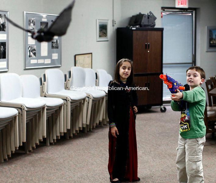 Thomaston, CT- 30 October 2013-103013CM02-  Josh Lovallo, 9, of Thomaston, takes aim at a bat with a Nerf Gun at the Thomaston library Wednesday afternoon.  Looking on is Mya Neri, 9, also of Thomaston.   The pair were reenacting a scene from The Ghosts' Grave, a book by Peg Kehret, which was part of library's Halloween series.  The event, put on by Denise Butwill children's librarian, featured games and a cake, both depicting scenes from the book.    Christopher Massa Republican-American