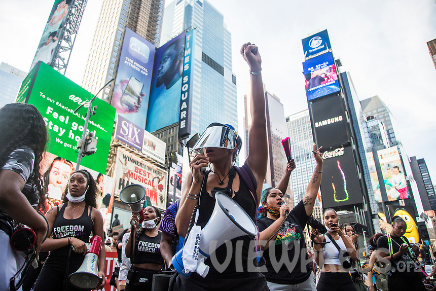 """NEW YORK, NY - JULY 26: A woman wearing face goggles directs the crowd of protesters in Times Square in New York, NY on July 26, 2020. Hundreds of New York activists participated in a march to condemn the They see it as an excessive focus of federal authorities in Portland, Oregon and continue to support the different movements of """"Black Lives Matter"""" (Photo by Pablo Monsalve / VIEWpress via Getty Images)"""