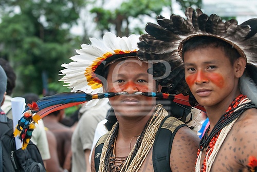 Two Rikbaktsa Indians with tribal decorations demonstrate during a march by indigenous people, the Landless People's Movement (MST) and other civil society groups in front of the Riocentro United Nations conference. The demonstrators are kept out of earshot and invisible to the UN conference. The United Nations Conference on Sustainable Development (Rio+20), Rio de Janeiro, Brazil, 20th June 2012. Photo © Sue Cunningham.