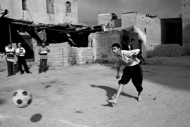 Baghdad, Iraq, April 4, 2003.As the American forces are reaching the outskirts of the city, young Baghdadis play football under the dark oil fires' smoke.