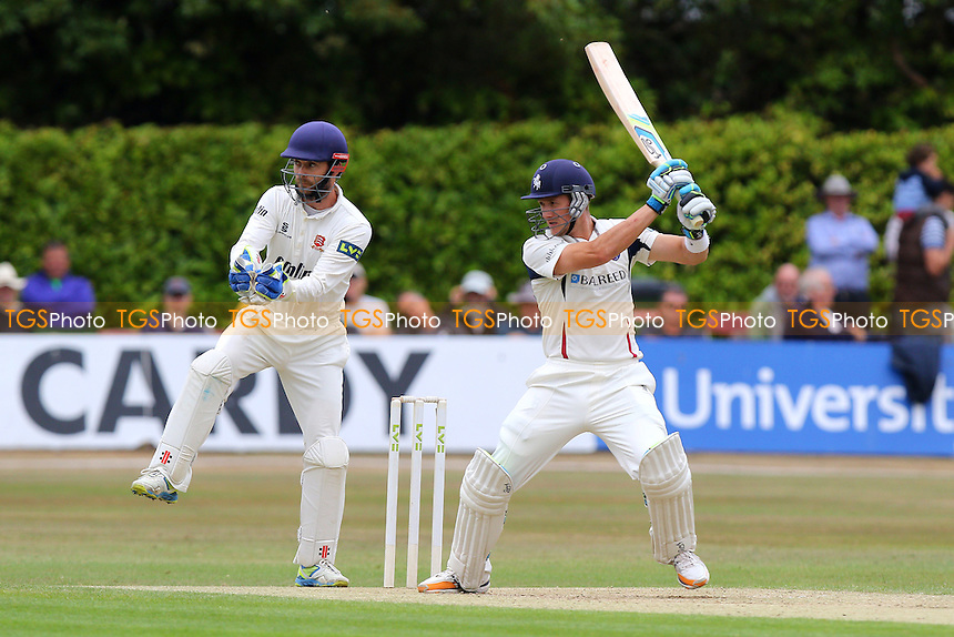 Joe Denly hits out for Kent CCC as James Foster looks on from behind the stumps