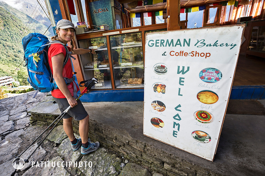 A female trekker stopped at a trailside bakery excited about eating some western food while trekking in to Annapurna Basecamp, Chomrong, Nepal.