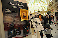 """A woman poses for a picture in the """"American Presidents Life Portraits"""" exhibit in the main hall of Union Station as hundreds gather in the hopes of catching a glimpse of the 44th U.S. President Barack Obama as his train pulled in after a day-long whistle stop tour of the northeast ahead of Tuesday's inauguration festivities in Washington DC on January 17, 2008."""