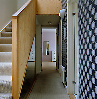 On this landing with wallpaper by Neisha Crosland a glass partition wall allows light to penetrate the staircase