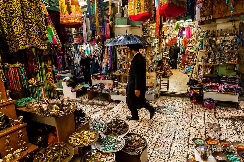 An orthodox Jew walking through the Arab bazaar (suq) in the old city of Jerusalem, Israel in the rain.