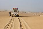 Namibia;  Namib Desert, Skeleton Coast, Northern Skeleton Coast National Park, 4x4 vehicle and tourist on dunes north of Moewe Bay