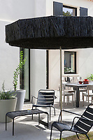 The terrace has an area for outdoor dining as well as a separate seating area shaded by a fringed parasol