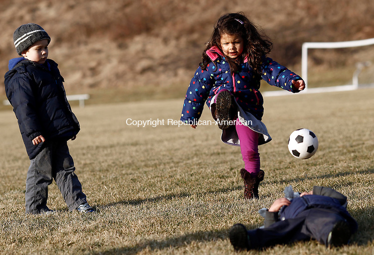 Middlebury, CT- 17 January 2014-011714CM01- Marielle De Jesus 4, of Naugatuck kicks the ball around her brother Alec De Jesus, 21 months as Nate Davis, 4, of Lexington, MA, looks at Meadowview Park in Middlebury on Friday.  The families, including Nate's sister Charlotte,  were enjoying the milder weather by kicking around the soccer ball.    Christopher Massa Republican-American
