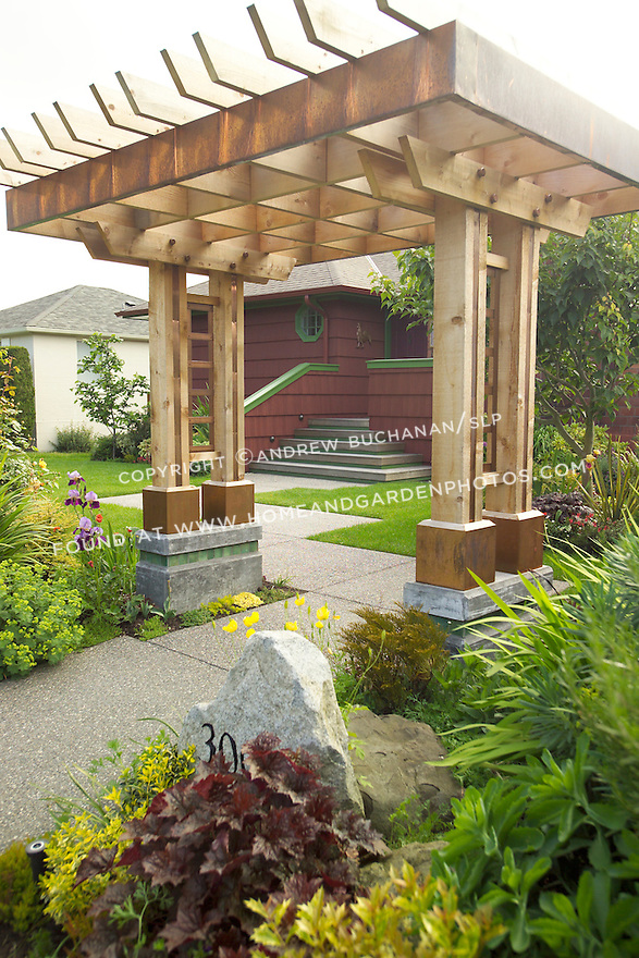 The entrance to this south and west facing organic garden in Seattle is through this distinctive entry arbor.  The owner, an artist and garden designer, has matched house and garden colors to tie the spaces together.