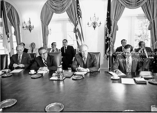 United States President Gerald R. Ford, just returning from his two day economic summit with leaders from six other nations, briefed his cabinet on the accomplishments and goals achieved at that meeting in the Cabinet Room of the White House in Washington, DC on June 29, 1976.  The leaders agreed to pursue the objective of sustained economic growth.  From left to right at the table: United States Secretary of the Interior Thomas Kleppe; United States Secretary of State Henry A. Kissinger; President Ford; and United States Secretary of Defense Donald Rumsfeld.  Visible in the background: Alan Greenspan, Chairman of the Council of Economic Advisors (behind Ford at left next to flag); and White House Chief of Staff Dick Cheney (far right looking out of the photo).<br /> Credit: Barry A. Soorenko / CNP