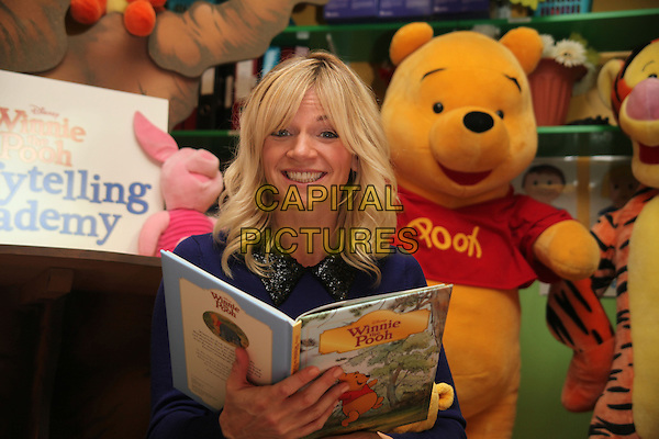 Zoe Ball .Photocall to launch Disney's Winnie the Pooh Storytelling Academy, London, England, UK, .3rd October 2012..half length black collar blue toy smiling sitting book .CAP/JEZ  .©Jez/Capital Pictures.