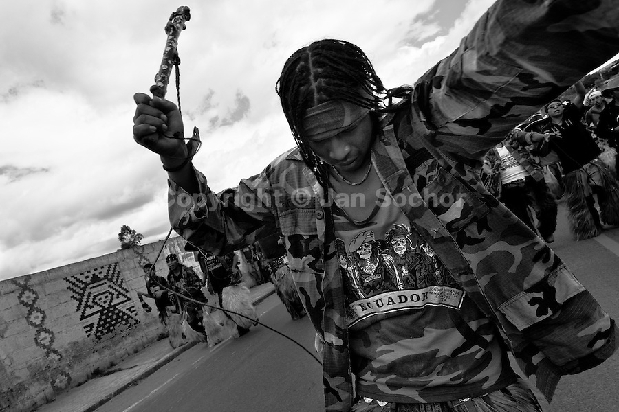 An Indian, wearing military camouflage, waves furiously the whip during the Inti Raymi (San Juan) festivities in Cotacachi, Ecuador, 24 June 2010. 'La toma de la Plaza' (Taking of the square) is an ancient ritual kept by Andean indigenous communities. From the early morning of the feast day, various groups of San Juan dancers from remote mountain villages dance in a slow trot towards the main square of Cotacachi. Reaching the plaza, Indians start to dance around. They pound in synchronized dance rhythm, shout loudly, whistle and wave whips, showing the strength and aggression. Dancers from either the upper communities (El Topo) or the lower communities (La Calera), joined in respective coalitions, seek to conquer and dominate the square and do not let their rivals enter. If not moderated by the police in time, the high tension between groups always ends up in violent clashes.