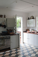 The focus of the simple kitchen is a hand-painted floor, the design copied from a magazine