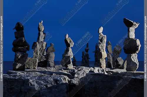 Stone human figures illuminated at night on a shore of lake Ontario in Toronto Inukshuk Inuit culture Spiritual symbol Atmospheric dramatic nighttime scenery