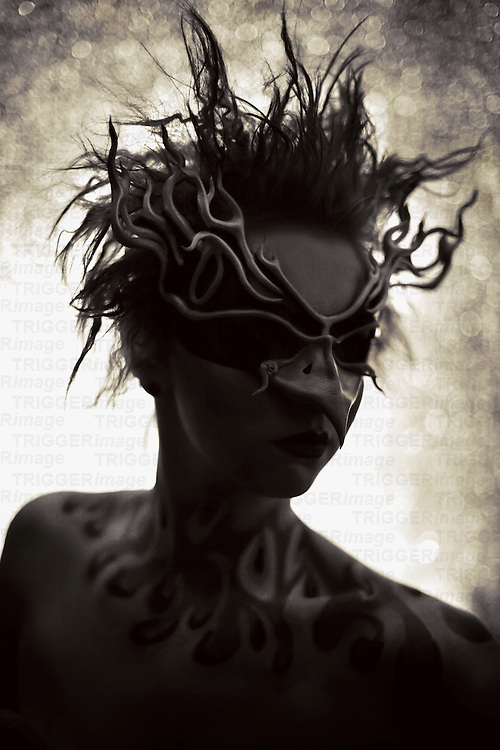 A young woman with fiery tattoos up her neck wearing a Phoenix mask