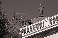 "A copper dome with clocks on each side sits in the center of the roof (Georgetown Courthouse) with a blindfolded statue of Themis on top, holding scales and a sword. Themis is described as ""of good counsel"", and is the embodiment of divine order, law, and custom."