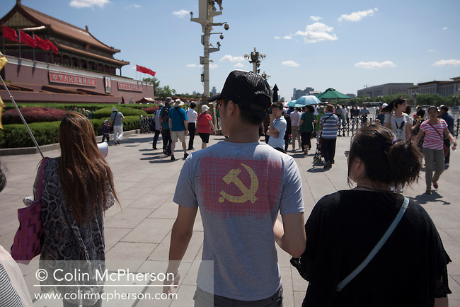 A man in a t-shirt with a hammer and sickle motif walking towards the Rostrum in Tiananmen Square, Beijing, China. Tiananmen Square is a large city square in the center of Beijing, China, named after the Tiananmen Gate (Gate of Heavenly Peace) located to its North, separating it from the Forbidden City. Tiananmen Square was the third largest city square in the world and is visited by tens of thousands of foreign and Chinese tourists each year.