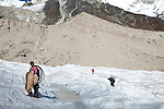 Members of the research team of Dr Shresth Tayal, Glaciologist at The Energy and Resources Institute (TERI) (from left)  Sanjay Balmiki , Phurbu Tsering Butia and Mohammad Ashraf Genai  carry equipment onto the fast reducing Rathong Glacier (centre of frame) below the 6678 meter Rathong Peak  in the North East Indian state of Sikkim close to the Nepalese border. Considered to be a themometre of the environment, it has been chosen by TERI to be a test case of environmental damage being done in India and China. Dr. Tayal is conducting three dimensional tests that include measuring the depth of the ice to form concrete conclusions on the fate of the glacier.The Indian Government is denying the glaciers' demise despite data suggesting it has been reduced by more than over 80% in the last 42 years.
