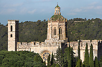 General view of the church of the Monestir de Santes Creus surrounded with trees, Aiguamurcia, Catalonia, Spain, pictured on May 21, 2006, in the morning. The Cistercian Reial Monestir Santa Maria de Santes Creus and its church were built between 1174 and 1225. Following strict Cistercian rule, the Romanesque complex originally featured no architectural embellishments with the exception of ornamented capitals and crenellations on the rooflines. In the 13th century parts of the abbey and the cloister were converted in Gothic style by James II of Aragon who also added the dome to the church. It is pictured from the east showing the rose window. The lantern on the dome is a Baroque addition. Picture by Manuel Cohen.