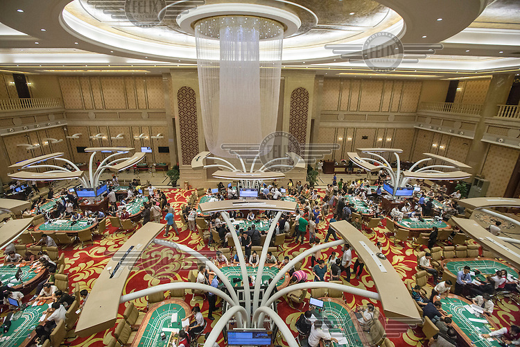 The interior of the Galaxyse casino which was built on the site of a former rice paddy on the outskirts of Mong La. A steady stream of taxis and people-carriers ferry customers at all hours to the casinos which are full of Chinese gamblers, including people playing remotely through surrogates with high-speed internet connections. Chinese authorities tend to turn a blind eye to this jungle sanctum, but in 2003, a large contingent of Chinese soldiers marched across the border and shut down five Chinese-run casinos. The daughter of a high-ranking Chinese government official sparked the incursion after she lost 1.4 million yuan ($168,674) at Mong La's gambling tables, according to Asia Times Online. <br /> The town of Mong La on the Burma - China border in western Burma (Myanmar) is technically in Burma but relies on most infrastructure - electricity, telecommunications - on neighbouring China. The main currency used here is the Chinese yuan. The town is in the middle of the so-called &quot;Golden Triangle&quot; and specialises in gambling and the sale of poached and endangered species. Tiger skins, rhino horns, pangolins and other creatures are freely traded here and many are available to eat. Prostitution is rife and just outside the town a bear farm keeps between 500 and 600 bears which are kept in captivity for their bile which is harvested for medicinal use.