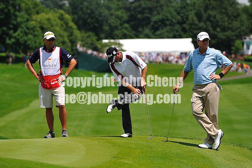 6/27/09 - Photo by John Cheng for Newsport.  3rd round of 2009 Travelers Championship takes place at TPC River Highlands in Cromewll, Connecticut.  Jerry Kelly checks his shoe while Scott Verplank looks on.