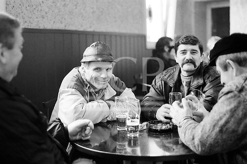 Katowice, Poland. Group of miners sitting around bar room table drinking beer from glasses.
