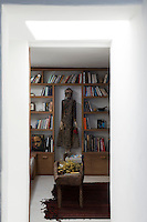 Built-in bookcases frame a carved Asian statue in the office