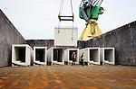 AMSTERDAM - In het Amsterdamse havengebied gaan enkele tientallen door Voorbij Prefab Beton gebouwde kabelkokers op transport voor de Sluiskiltunnel in Zeeland. In opdracht van Combinatie BAM en TBI infra bouwt het Amsterdamse bedrijf 780 kabelkokers voor de geboorde verkeerstunnel onder het Kanaal van Gent naar Terneuzen. De bijna 13 ton zware kabelkokers worden vervoerd in samenwerking met De Eendracht. COPYRIGHT TON BORSBOOM