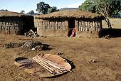 Lolgorian, Kenya. Siria Maasai Manyatta; adobe mud walled houses with dung pile, cow hide and sticks prepared for building.